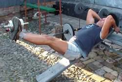 Подъем ног на наклонной доске с гантелью